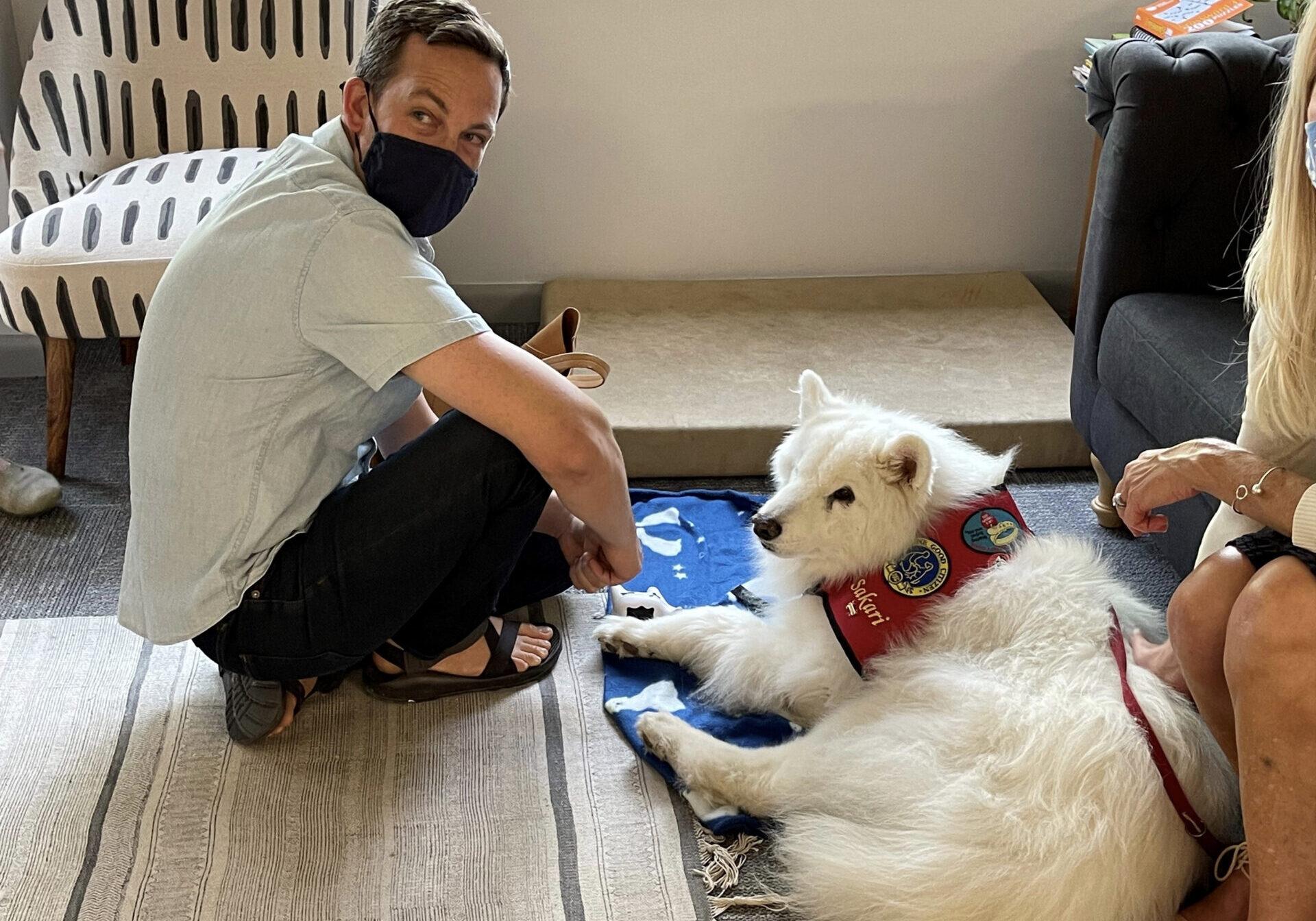CO Senate Majority Leader Steve Fenberg bonds with comfort dog Sakari.